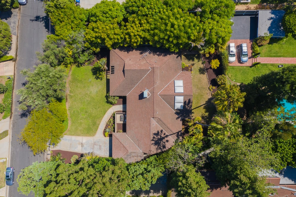This is an aerial view of the house with an earthy tone to its roof complemented by the green trees surrounding the house. Image courtesy of Toptenrealestatedeals.com.