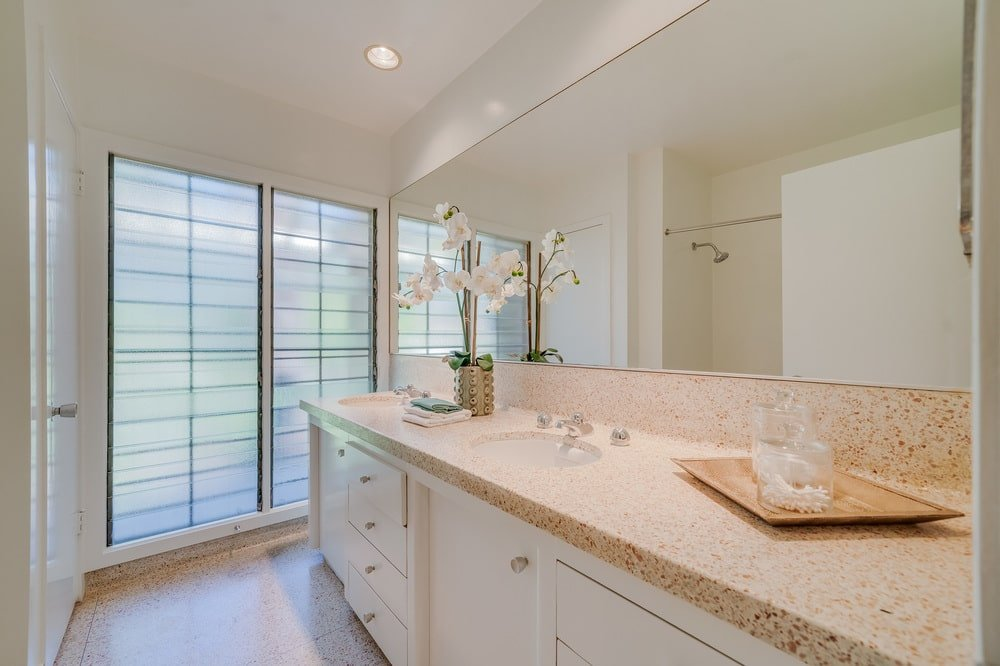 This is a look at the large two-sink vanity of the bathroom with a beige countertop that pairs well with the white cabinetry. Image courtesy of Toptenrealestatedeals.com.