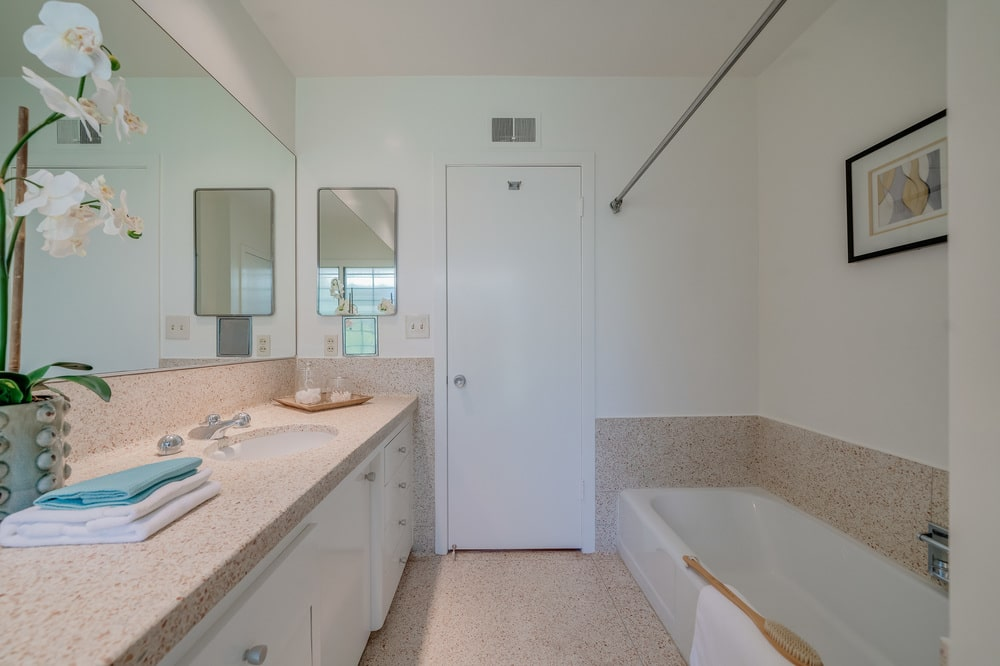 The light tone of the walls and ceiling of this bathroom is complemented by the beige floor, countertop and backsplash. Image courtesy of Toptenrealestatedeals.com.