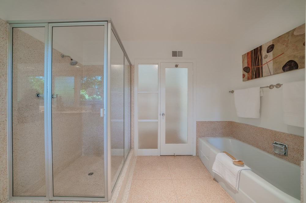 This bathroom has a couple of sliding glass doors in between the glass-enclosed shower area and the bathtub. Image courtesy of Toptenrealestatedeals.com.