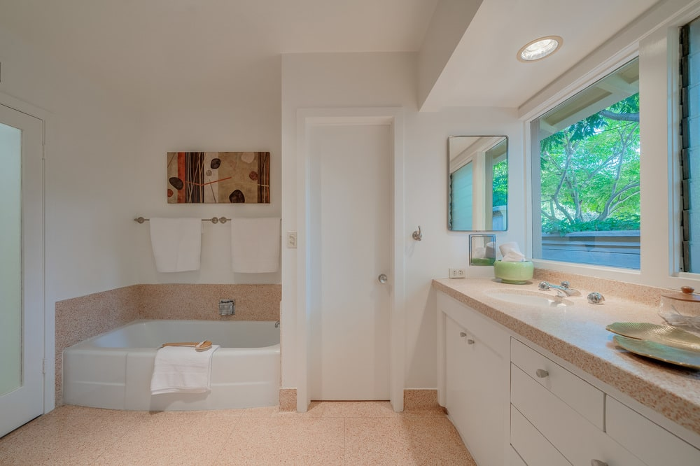 This is a view of the bathroom showcasing the beige tones of the floor, walls and vanity complemented by the natural lights coming in from the windows. Image courtesy of Toptenrealestatedeals.com.