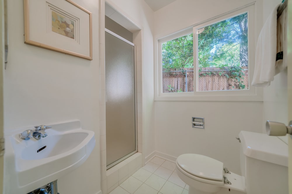 This other bathroom has a walk-in shower area with a frosted glass door across from the toilet. Image courtesy of Toptenrealestatedeals.com.