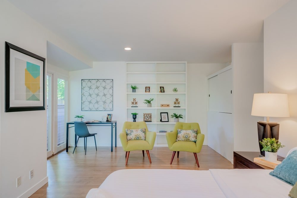 This angle of the bedroom showscases the pair of green armchairs and the work area at the corner. Image courtesy of Toptenrealestatedeals.com.