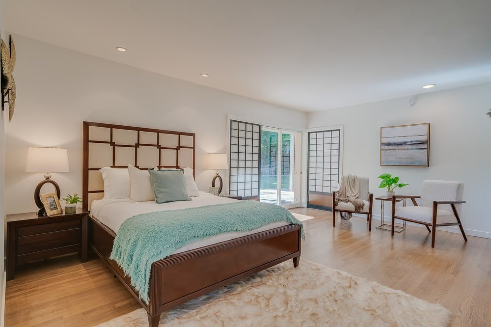 This other bedroom has a wooden bed with a decorative headboard that stands out against the beige wall and matches the doors on the side. Image courtesy of Toptenrealestatedeals.com.