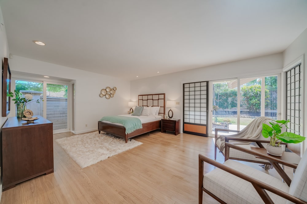 This view of the bedroom shows the large doors on the side leading to the back of the house. Image courtesy of Toptenrealestatedeals.com.