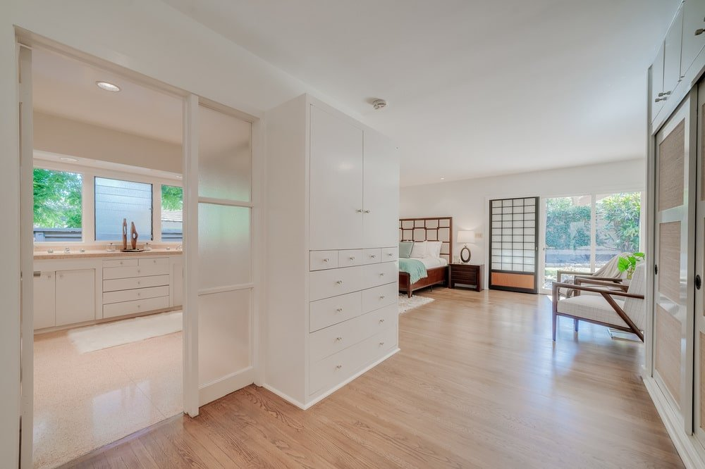 This angle of the bedroom shows the entryway to the bathroom with frosted glass doors. Image courtesy of Toptenrealestatedeals.com.