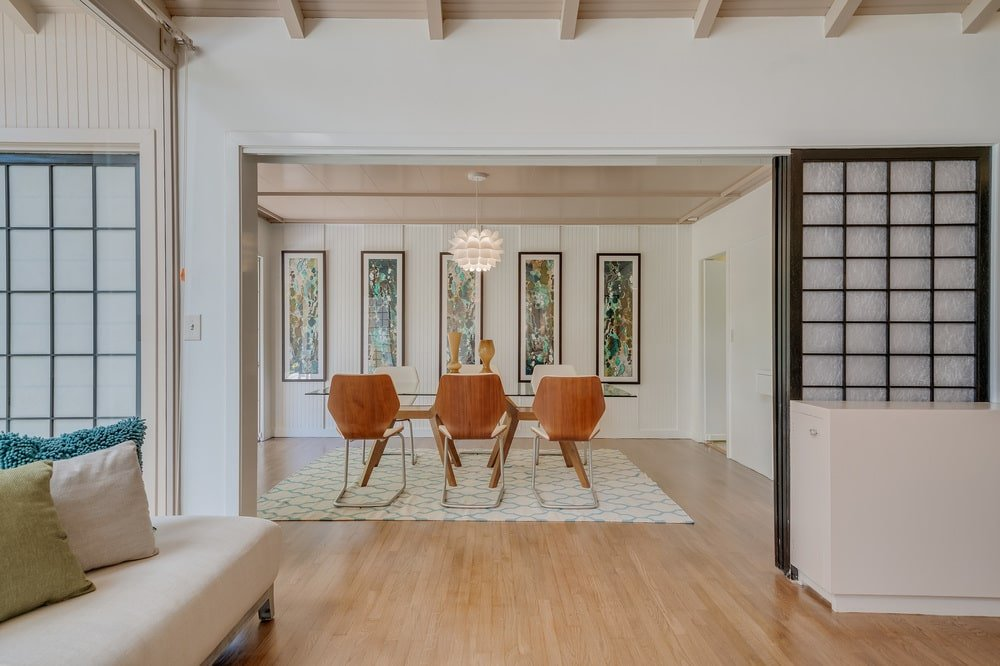 This is the entryway to the dining room that has a dining table surrounded by modern chairs. Image courtesy of Toptenrealestatedeals.com.