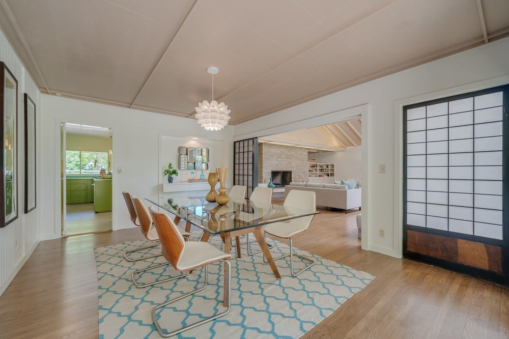 This other look at the dining room showcases the rectangular glass-top dining table on the patterned area rug. Image courtesy of Toptenrealestatedeals.com.
