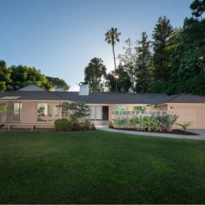 This is the front view of the house showcasing the leach tone to its exterior walls complemented by the grass lawn. Image courtesy of Toptenrealestatedeals.com.