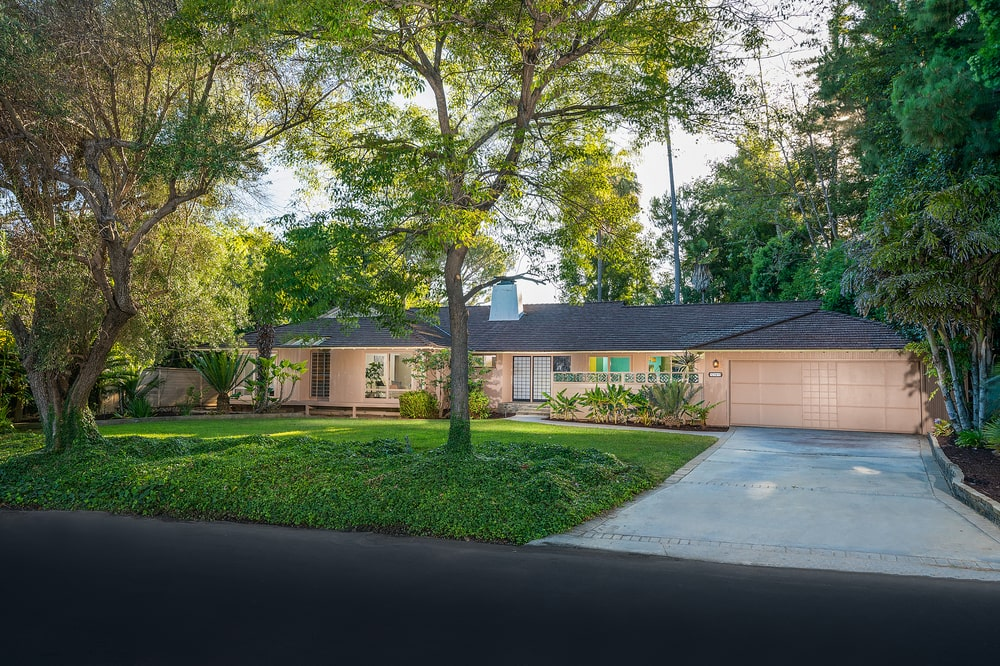 This is a front view of the house showcasing the peach tone of the exteriors complemented by the concrete driveway and grass lawn. Image courtesy of Toptenrealestatedeals.com.