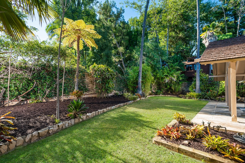This is a look at the backyard garden with a grass lawn and various trees. Image courtesy of Toptenrealestatedeals.com.