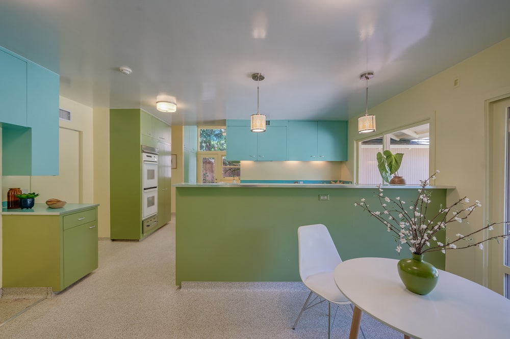 This is the kitchen with green cabinetry and turquoise floating cabinets. Image courtesy of Toptenrealestatedeals.com.