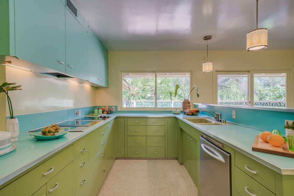 This is a closer look at the U-shaped peninsula of the kitchen with green cabinetry complemented by turquoise accents. Image courtesy of Toptenrealestatedeals.com.