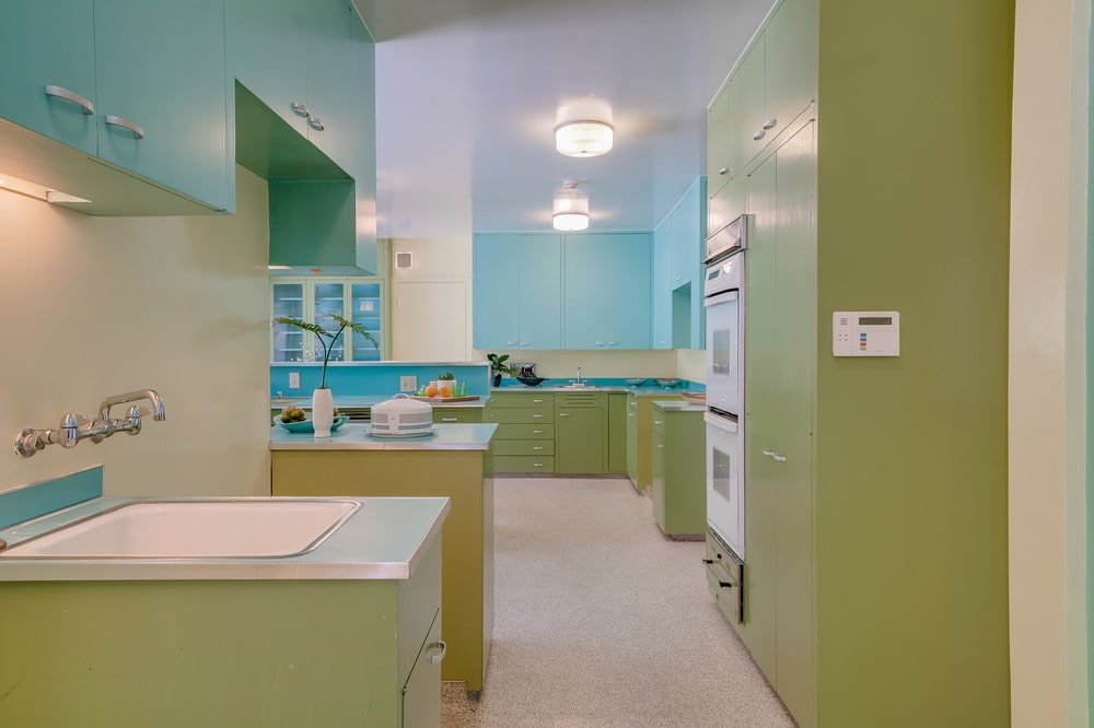 This other view of the kitchen shows the light beige flooring that complements the green cabinetry. Image courtesy of Toptenrealestatedeals.com.