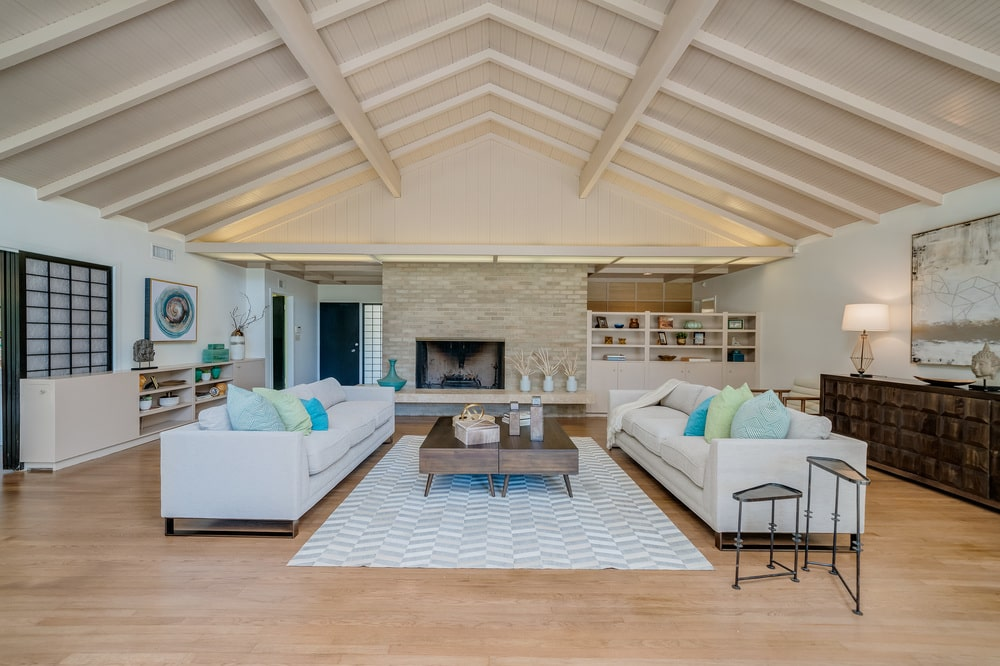 This is the living room with a couple of sofas flanking a wooden coffee table on a light area rug. Image courtesy of Toptenrealestatedeals.com.