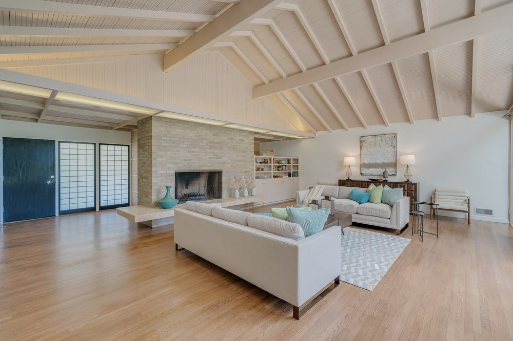 This other view of the living room shows the large stone wall housing the fireplace at the far end. Image courtesy of Toptenrealestatedeals.com.
