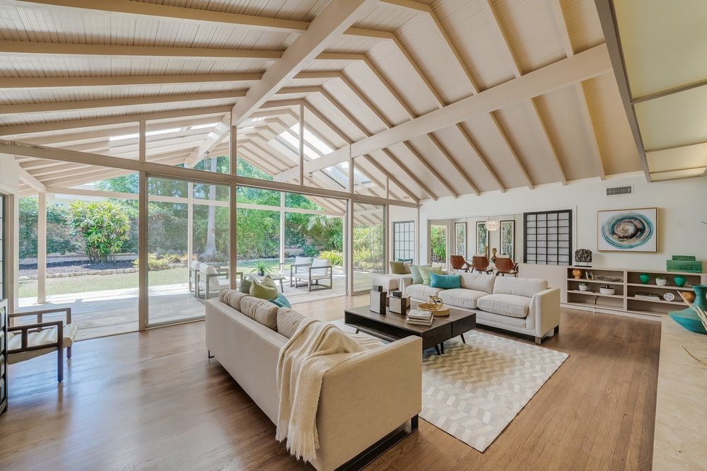 This angle of the living room shows the tall wooden cathedral ceiling and massive glass walls. Image courtesy of Toptenrealestatedeals.com.