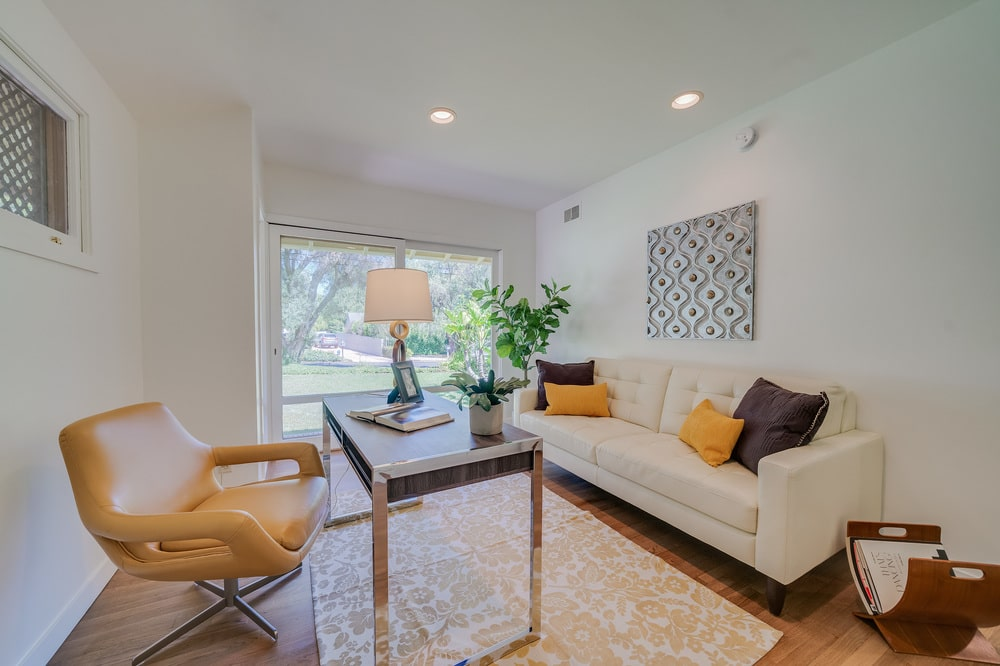 The home office has beige walls that match the beige sofa across from the desk and swivel chair. Image courtesy of Toptenrealestatedeals.com.