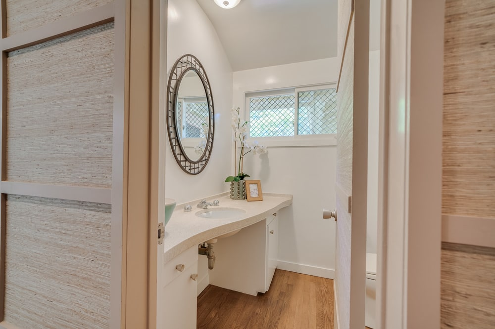 This is the powder room with a small beige vanity and a round wall-mounted mirror. Image courtesy of Toptenrealestatedeals.com.