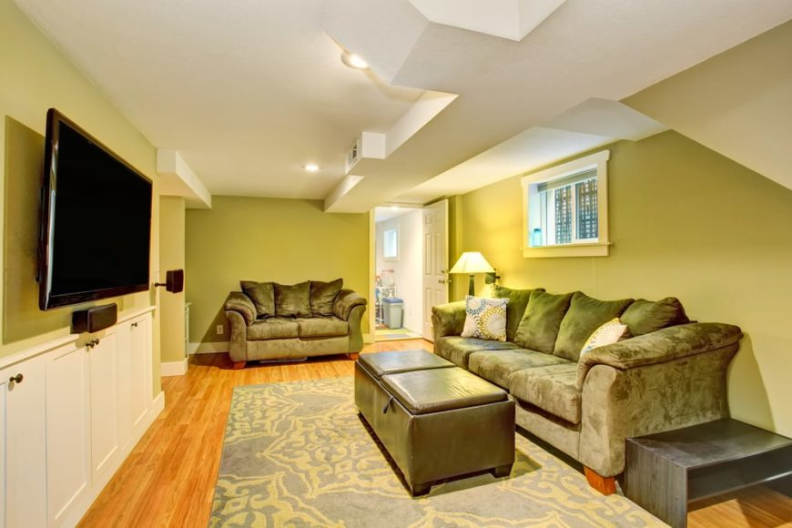 This family room has green walls, gray couches and a white ceiling to match the wainscoting.