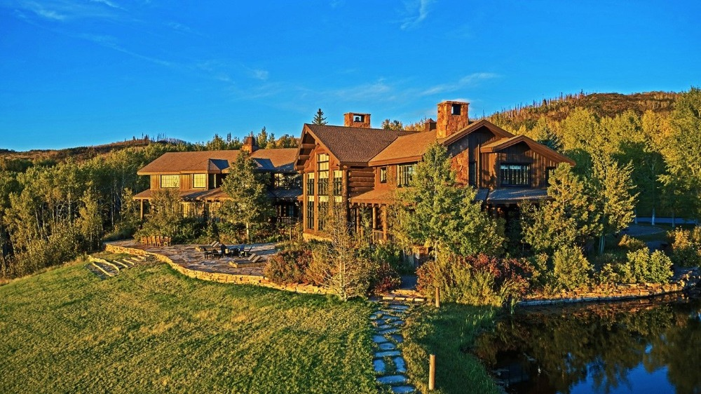 Outside view of the house showcasing its stunning rustic exterior and the beautiful landscape surrounding it. Image courtesy of Toptenrealestatedeals.com.