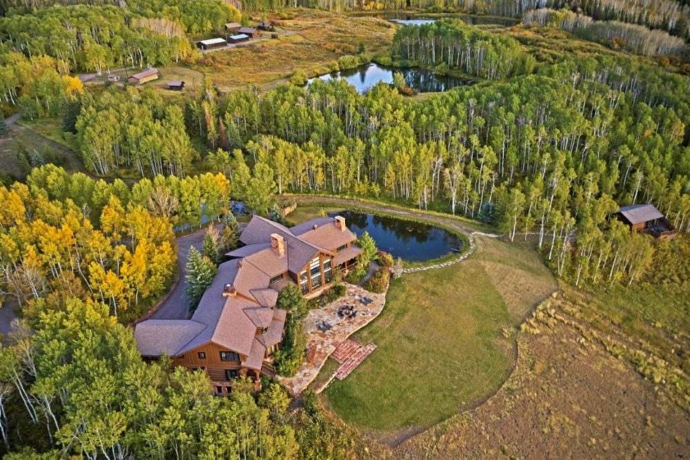 Aerial view of the property showcasing the main house and the gorgeous landscape surrounding it. Image courtesy of Toptenrealestatedeals.com.