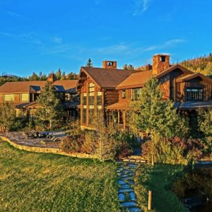 Exterior view of the house showcasing its rustic architecture and the beautiful greenery surrounding it. Image courtesy of Toptenrealestatedeals.com.