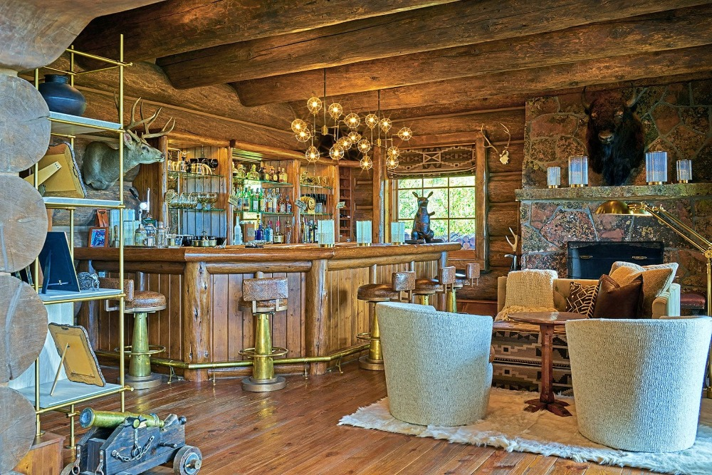A bar area with a living space featuring a fireplace on the side. Image courtesy of Toptenrealestatedeals.com.