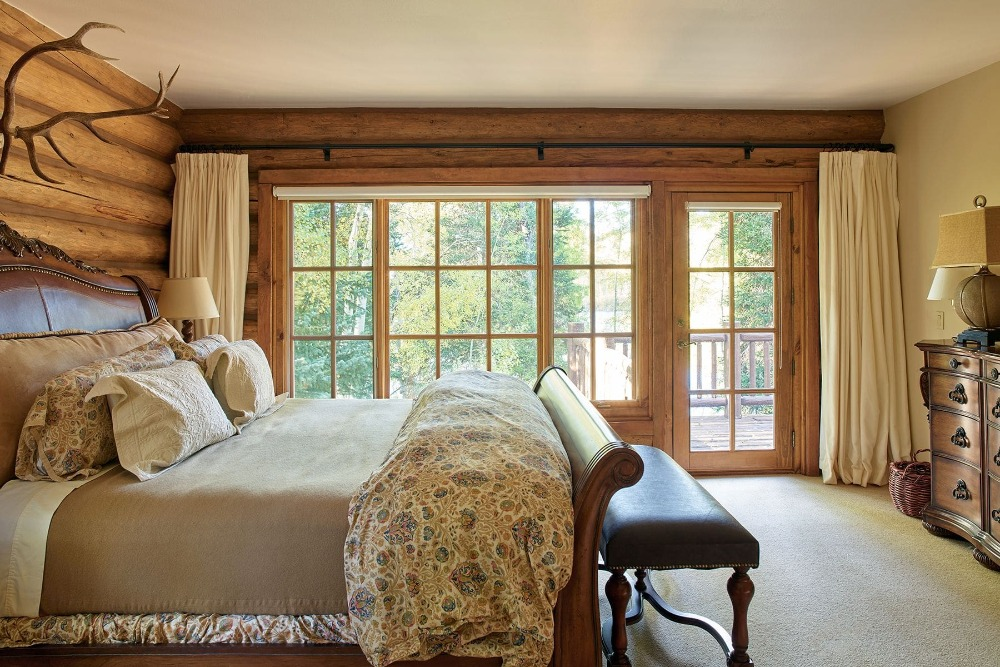 Bedroom with rustic walls and a classy bed set lighted by table lamps. Image courtesy of Toptenrealestatedeals.com.