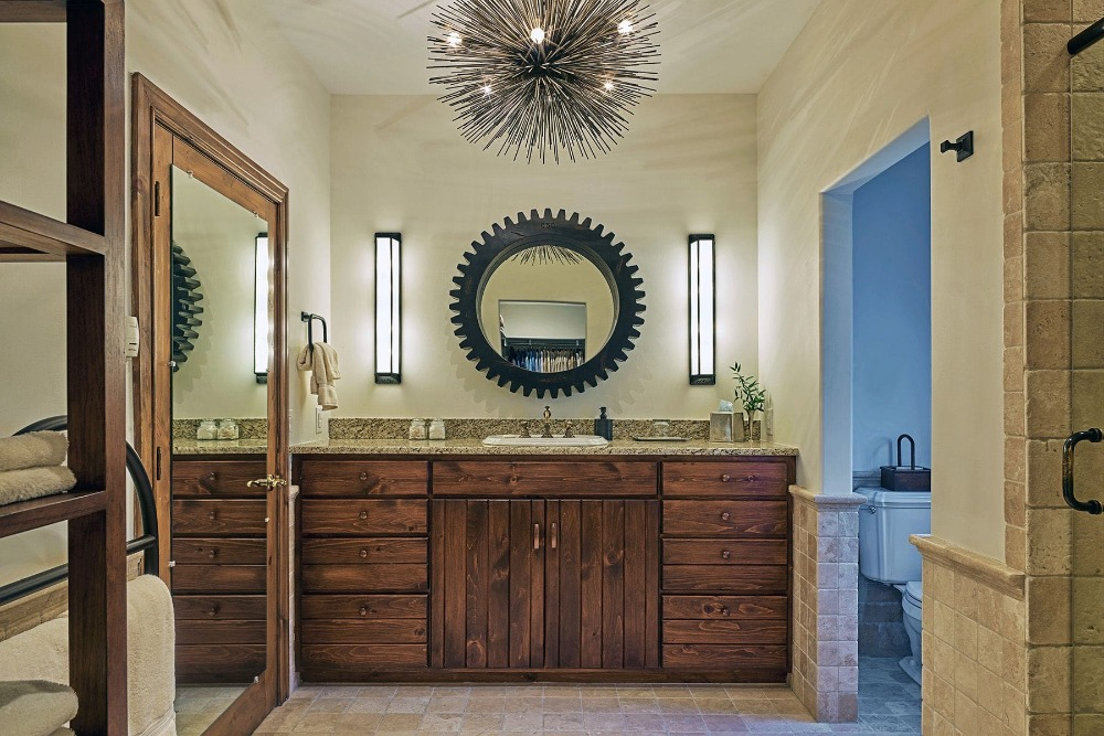 Another bathroom featuring a sink counter with built-in rustic cabinetry, along with a toilet room. Image courtesy of Toptenrealestatedeals.com.