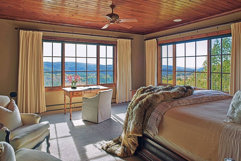 Bedroom with a study desk and chair set near the windows overlooking the stunning outdoor surroundings. Image courtesy of Toptenrealestatedeals.com.