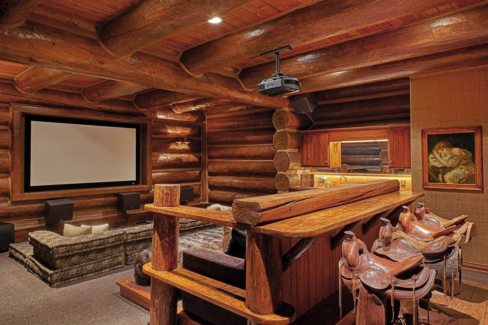 Home theater with a cozy sofa set along with a stylish bar counter and stools at the back. Image courtesy of Toptenrealestatedeals.com.