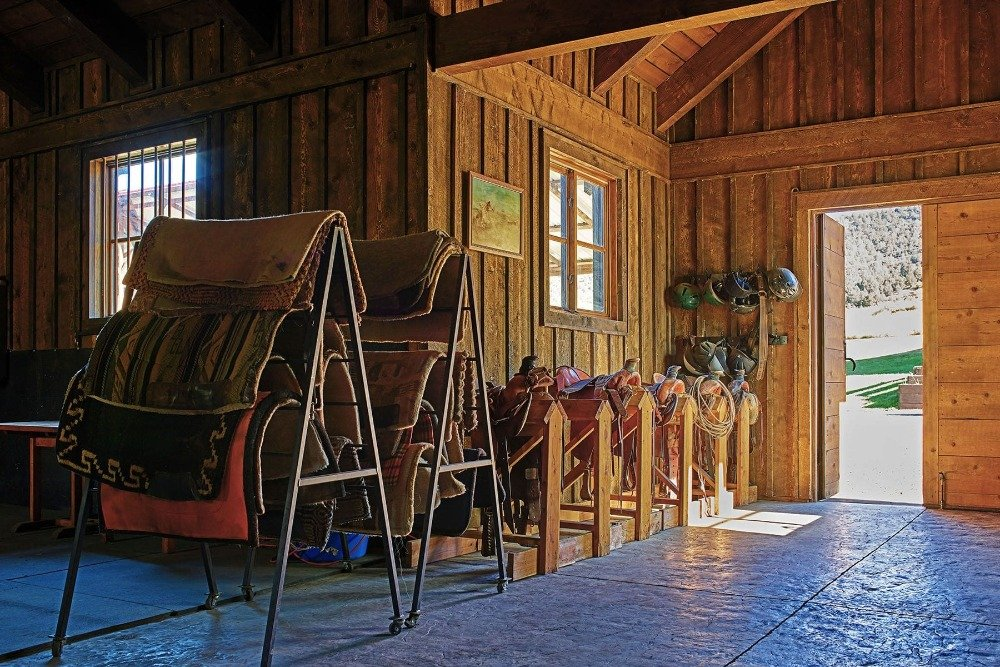 This structure with wooden walls and a high wooden ceiling houses some equipment that can be used inside the ranch. Image courtesy of Toptenrealestatedeals.com.
