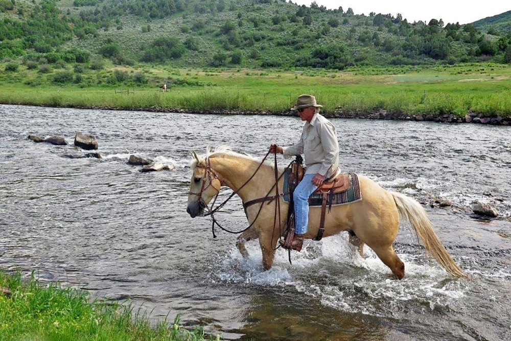 Greg Norman riding a horse, crossing the river. Image courtesy of Toptenrealestatedeals.com.