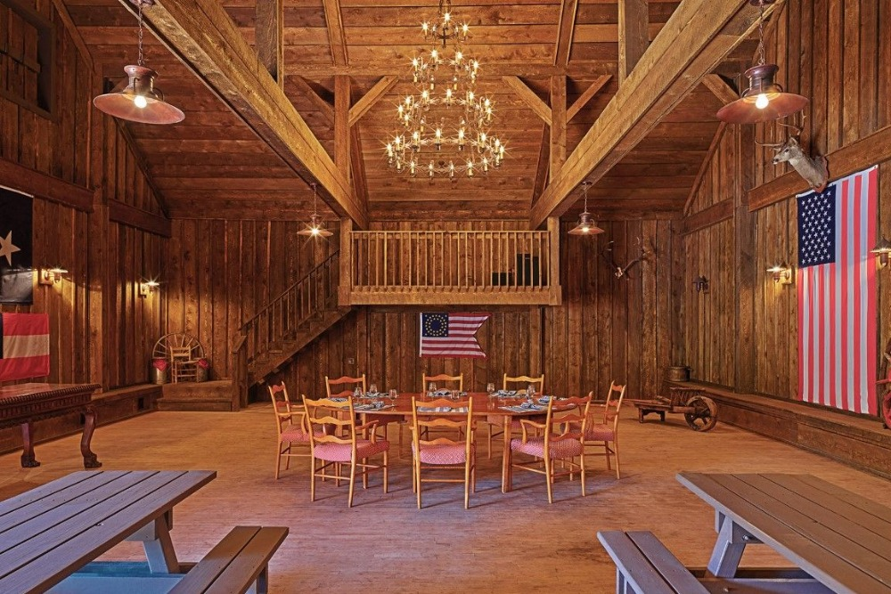 The banquet hall features a magnificent chandelier lighting the space. There's a round table set and multiple wooden rectangular table sets with bench seating. Image courtesy of Toptenrealestatedeals.com.
