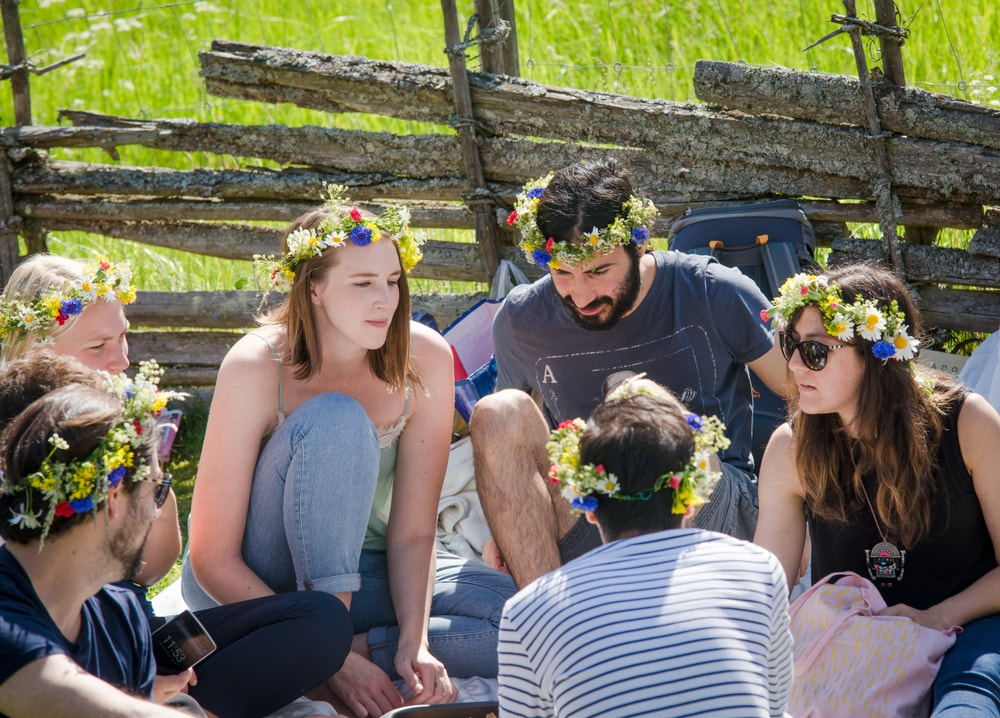 A group of friends sitting on the ground outdoors and wearing flower headbands.
