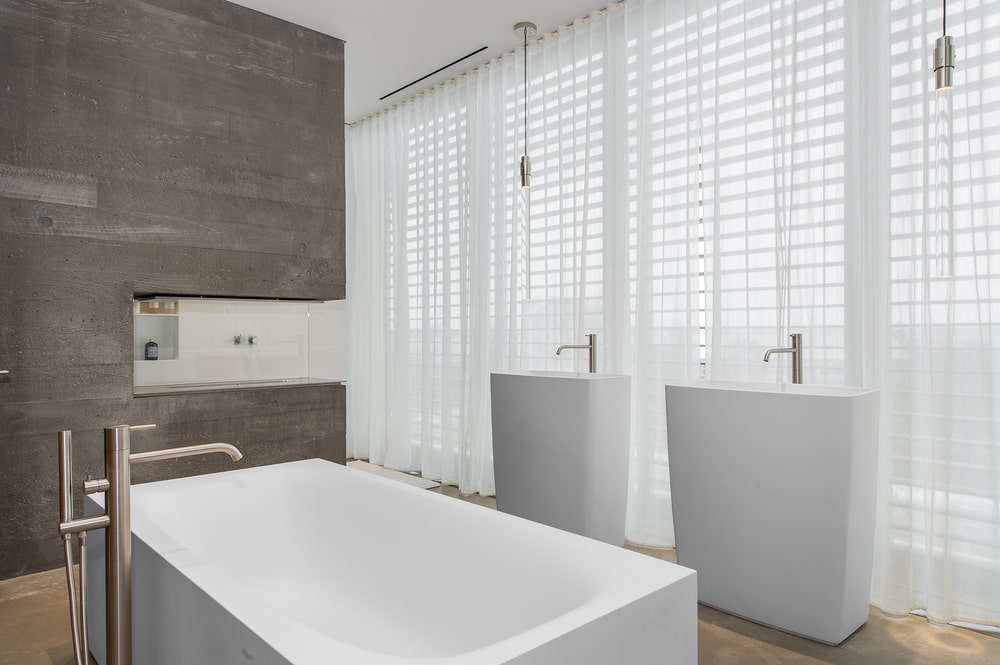 This bathroom has two pedestal sinks across from the bathtub. All of these are complemented by the bright natural lights of the glass walls. Image courtesy of Toptenrealestatedeals.com.