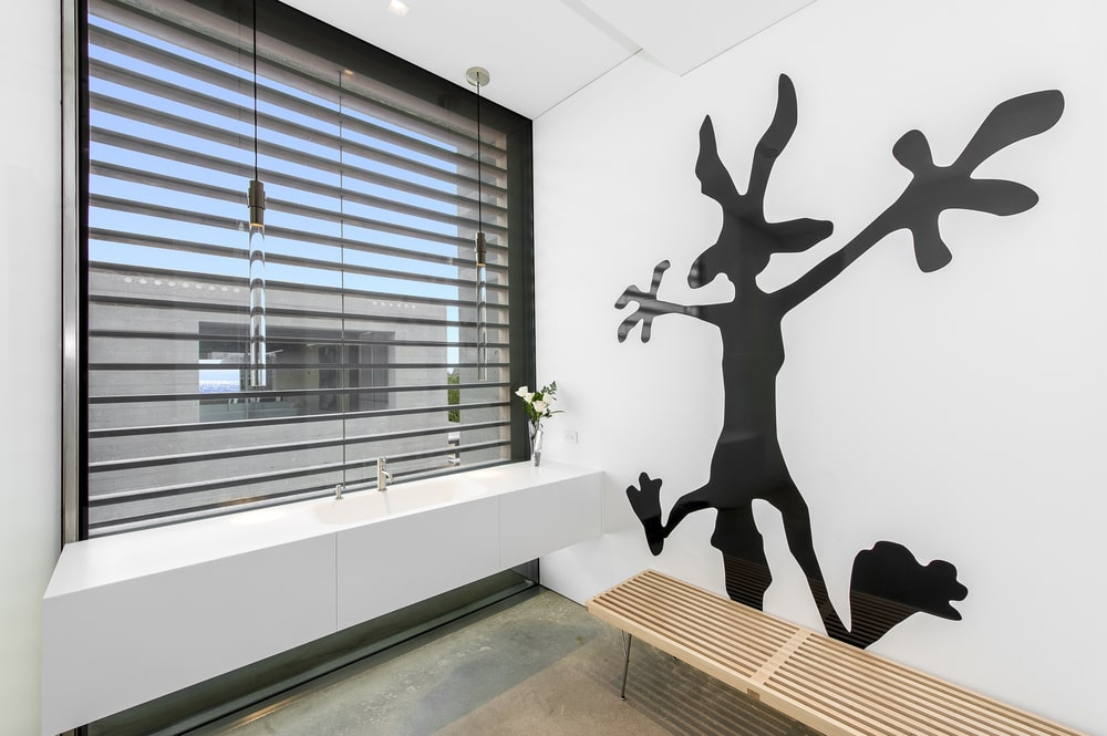 The kid's bathroom has a large mural of a cartoon character beside the large sink. Image courtesy of Toptenrealestatedeals.com.