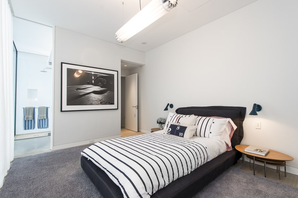 This other bedroom has a black platform bed that stands out against the white walls and complements the gray floor. Image courtesy of Toptenrealestatedeals.com.