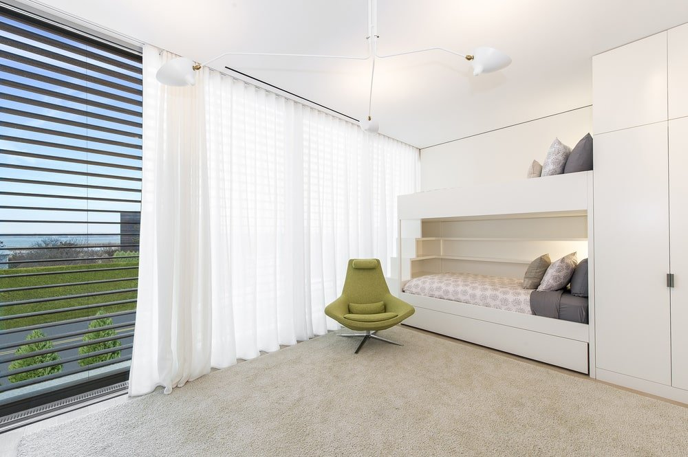 This is the children's bedroom with a double-deck bed built into the wall. This is paired with a green armchair and white curtains. Image courtesy of Toptenrealestatedeals.com.