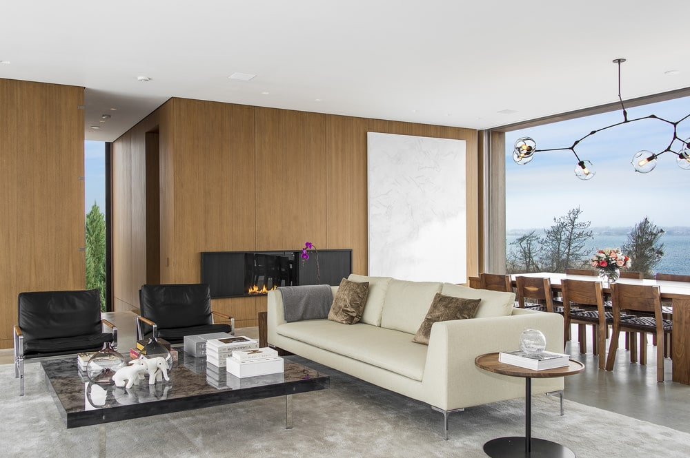 This angle of the great room shows the dining area behind the beige sofa. This is then complemented by a glass wall. Image courtesy of Toptenrealestatedeals.com.