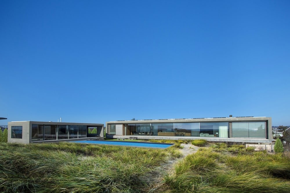 This is a look at the front of the house. Here you can see the glass walls that open the interiors of the house to the surrounding landscape.