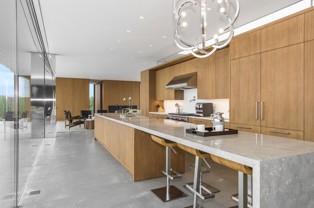 This is the kitchen with a long king island that has an extension on its countertop to form a breakfast bar topped with a chandelier. Image courtesy of Toptenrealestatedeals.com.