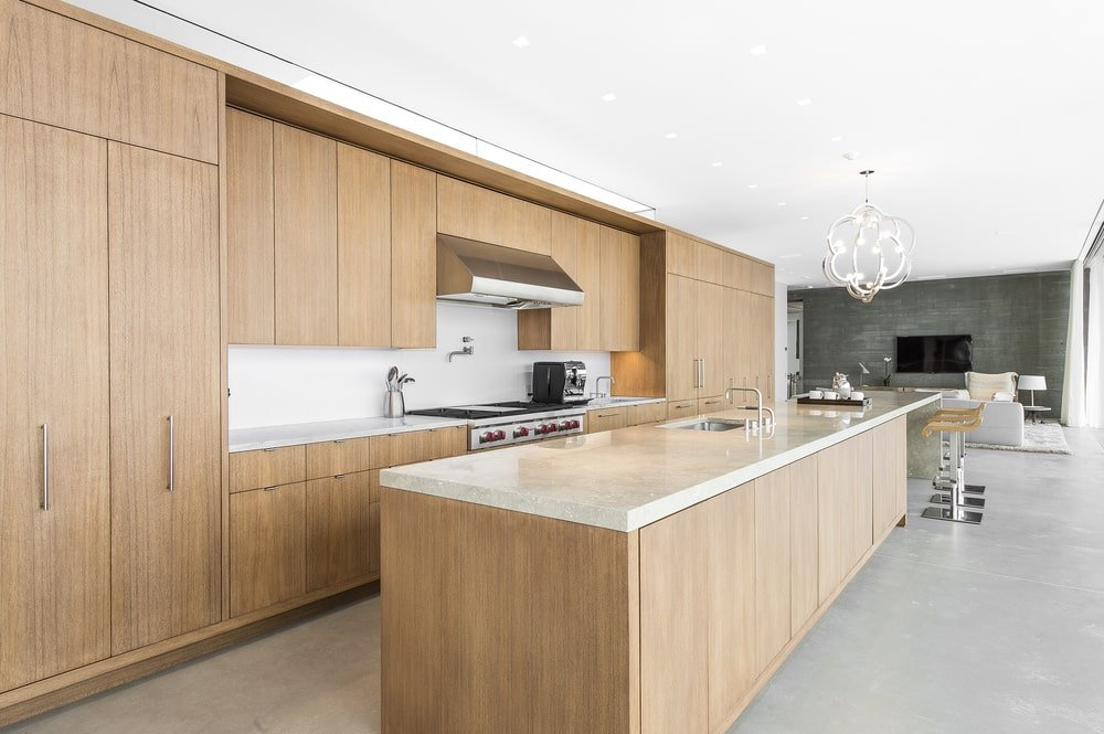 This other view of the kitchen shows the wooden cabinetry lining the walls across from the kitchen island. This is where the cooking area is placed. Image courtesy of Toptenrealestatedeals.com.