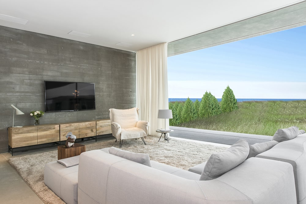 This other look at the living room shows that the large sectional L-shaped sofa is facing a concrete wall with a wall-mounted TV. Image courtesy of Toptenrealestatedeals.com.
