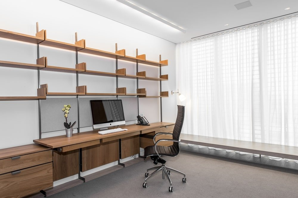 This is the home office with dark wooden structures that have built-in desks and shelves that stand out against the bright white walls and ceiling. Image courtesy of Toptenrealestatedeals.com.