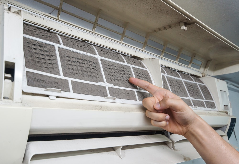 Hand pointing to a dirty air conditioner filter.