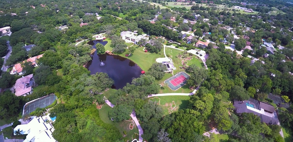 This is an aerial view of the property showing the landscaping that has large grass lawns, tall trees and a large pond. Image courtesy of Toptenrealestatedeals.com.