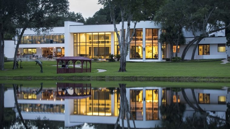 This is a view of the mansion from the vantage of the pond. You can see here the large glass walls of the house that glow warmly from the interior lights. The exterior of the house is then complemented by the landscaping that has lawns and tall trees. Image courtesy of Toptenrealestatedeals.com.