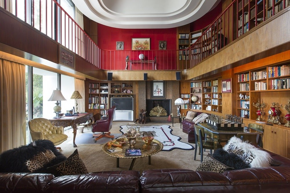 The two-story library has a tall white cove ceiling contrasted by red walls. These are then complemented by the wooden bookshelves lining the walls along with a large glass wall on one side. Image courtesy of Toptenrealestatedeals.com.